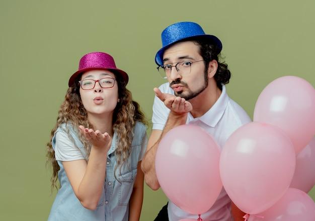 Erfreutes junges paar, das rosa und blauen hut trägt, der hinter luftballons steht und kussgeste zeigt