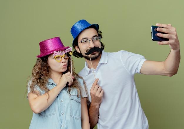 Erfreutes junges paar, das rosa und blauen hut trägt, nehmen ein selfie-mädchen, das maskerade-augenmaske auf stock hält und kerl, der falschen schnurrbart auf stock hält