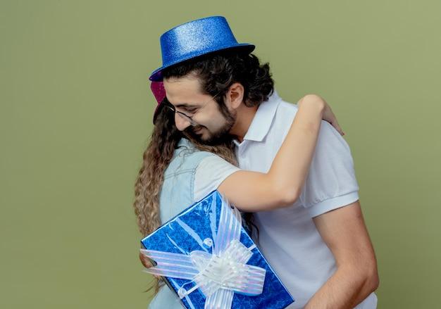 Erfreutes junges paar, das rosa und blauen hut trägt, umarmen sich und kerl, der geschenkbox hält