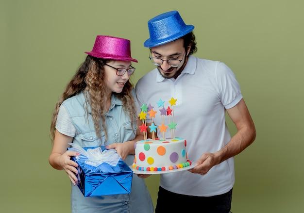 Erfreutes junges paar, das rosa und blauen hutmädchen hält geschenkbox und kerl hält und mit mädchen an geburtstagstorte schaut