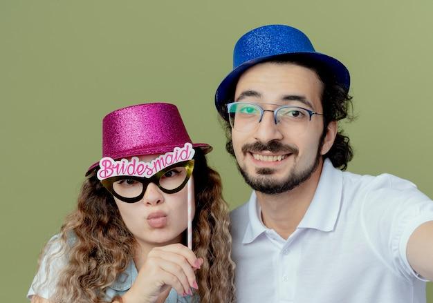 Erfreutes junges paar, das rosa und blaues hutmädchen hält, das maskerade-augenmaske auf stock und kerl hält kamera lokalisiert auf olivgrünem hintergrund hält