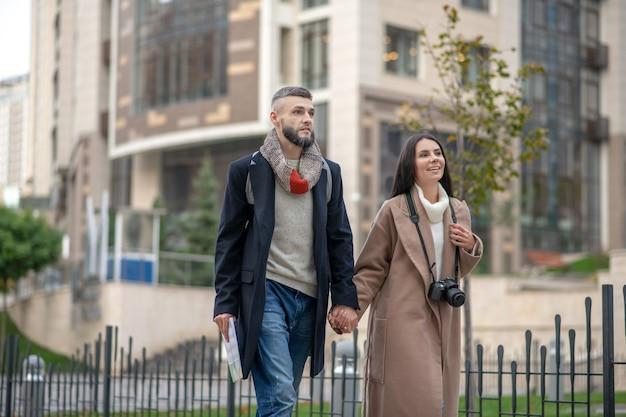 Erfreutes junges paar, das seine zeit genießt, während es einen tollen spaziergang in der nachbarschaft macht