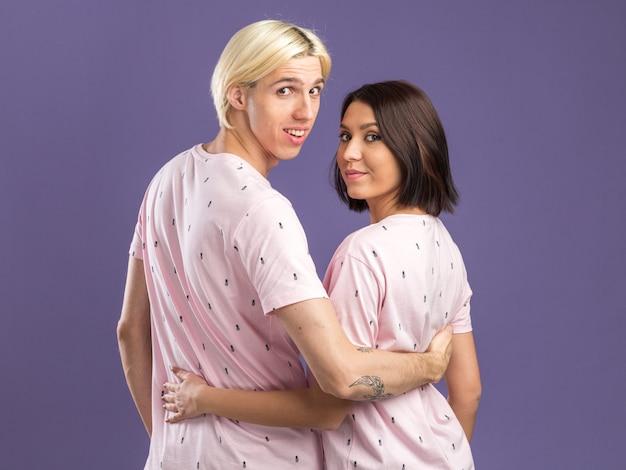 Erfreutes junges paar im pyjama, das hinter der ansicht steht und sich die hand auf den rücken legt und die vorderseite isoliert auf der lila wand betrachtet