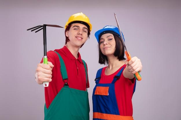 Erfreutes junges paar in der bauarbeiteruniform und im schutzhelm, die im profilansicht-kerl stehen, der hoerake-mädchen ausstreckt, das handsäge ausstreckt
