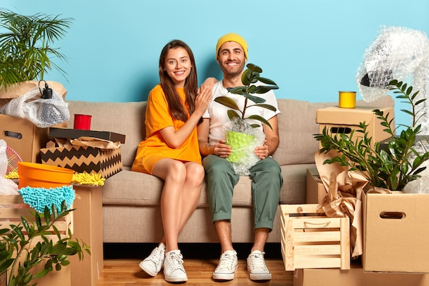 Erfreutes junges paar sitzt auf der couch, umgeben von kisten