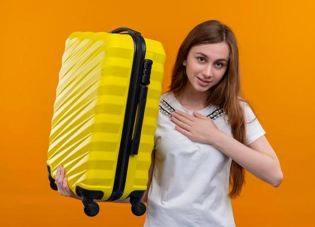 Erfreutes junges reisendes mädchen, das koffer hält und hand auf brust auf lokalisiertem orange raum setzt