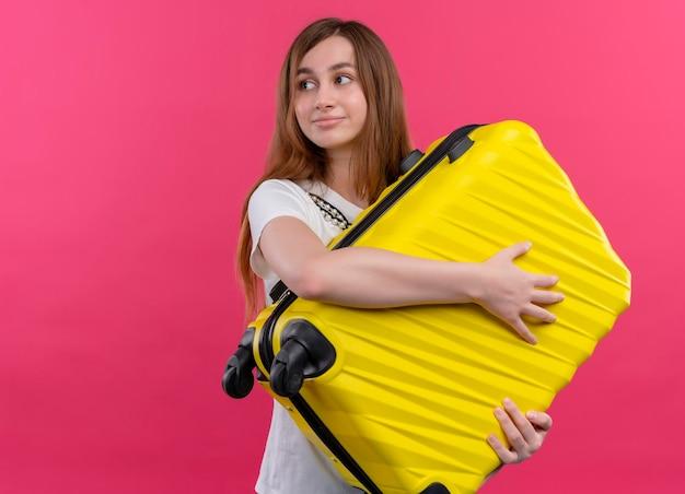 Erfreutes junges reisendes mädchen, das koffer hält und linke seite auf isoliertem rosa raum mit kopienraum betrachtet