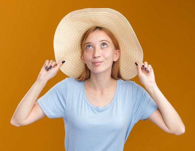 Erfreutes junges rothaariges ingwermädchen mit sommersprossen, die strandhut tragen und auf orange schauen