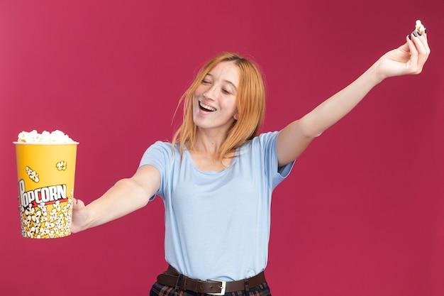 Erfreutes junges rothaariges ingwermädchen mit sommersprossen hält popcorn-eimer