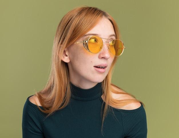 Erfreutes junges rothaariges ingwermädchen mit sommersprossen in sonnenbrille, das auf die seite schaut