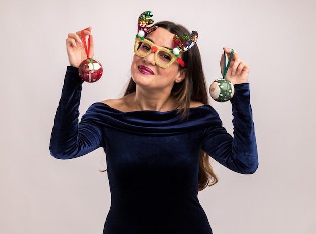 Erfreutes junges schönes mädchen, das blaues kleid und weihnachtsbrille hält, die weihnachtskugeln lokalisiert auf weißem hintergrund hält