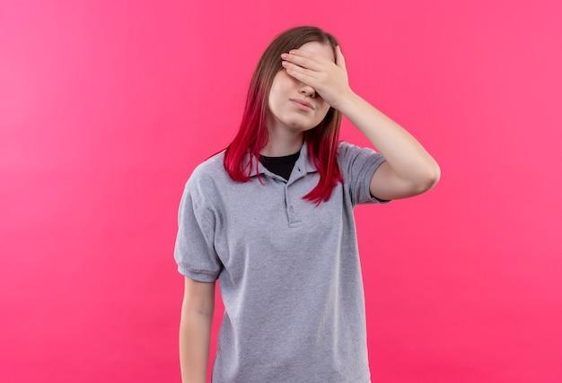 Erfreutes junges schönes mädchen, das graue t-shirt bedeckte augen mit hand auf lokalisiertem rosa hintergrund trägt