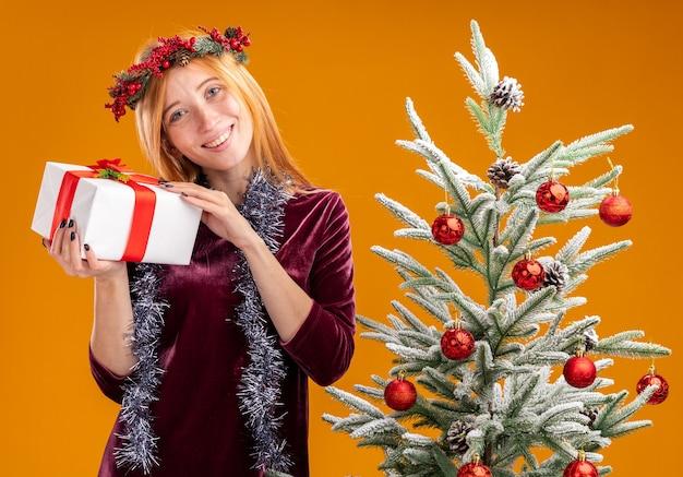 Erfreutes junges schönes mädchen, das in der nähe einen weihnachtsbaum trägt und ein rotes kleid und einen kranz mit girlande am hals trägt, die eine geschenkbox isoliert auf einer orangefarbenen wand hält