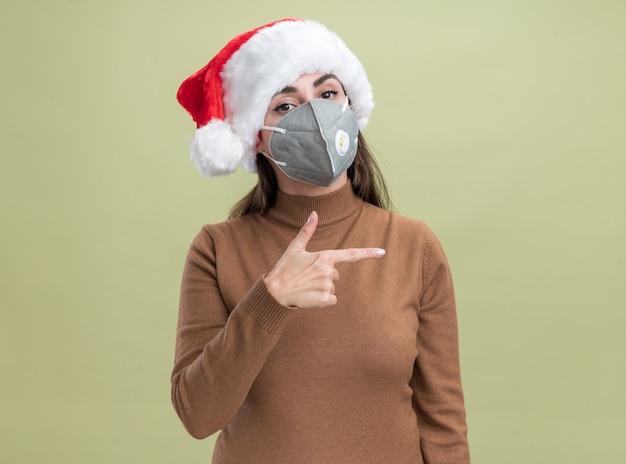 Erfreutes junges schönes mädchen, das weihnachtshut mit medizinischen maskenpunkten an der seite lokalisiert auf olivgrünem hintergrund mit kopienraum trägt