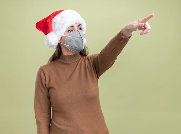 Erfreutes junges schönes mädchen, das weihnachtshut mit medizinischen maskenpunkten an der seite lokalisiert auf olivgrünem hintergrund trägt