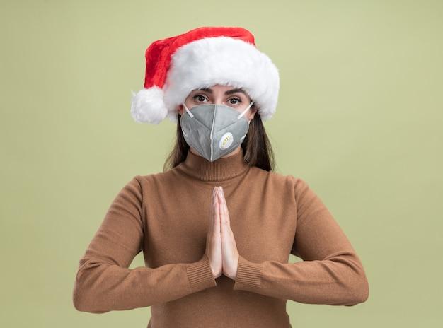 Erfreutes junges schönes mädchen, das weihnachtshut mit medizinischer maske trägt, die gebetsgeste auf olivgrünem hintergrund zeigt