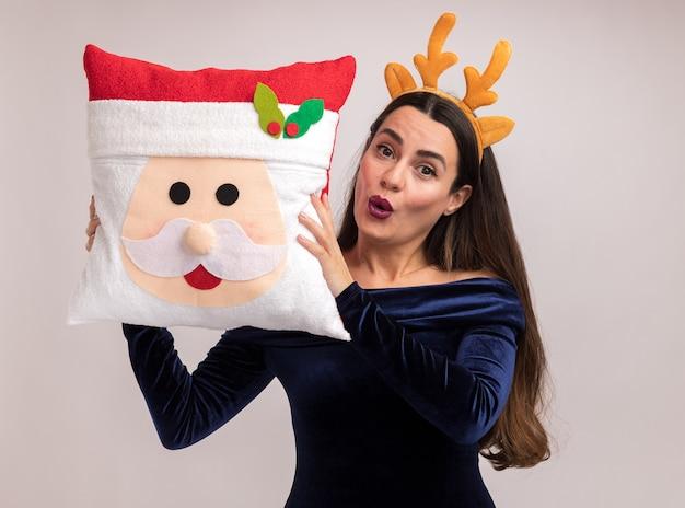 Erfreutes junges schönes mädchen mit blauem kleid und weihnachtshaarreifen, das weihnachtskissen um das gesicht isoliert auf weißer wand hält