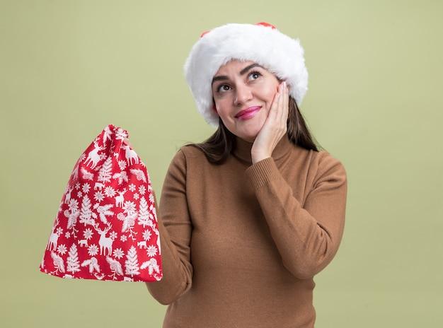 Erfreutes junges schönes mädchen mit weihnachtsmütze, das eine weihnachtstasche hält und die hand auf die wange legt, isoliert auf olivgrüner wand?