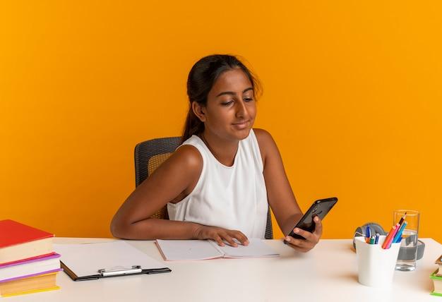 Erfreutes junges schulmädchen, das am schreibtisch mit den schulwerkzeugen sitzt und telefon lokalisiert auf orange wand hält