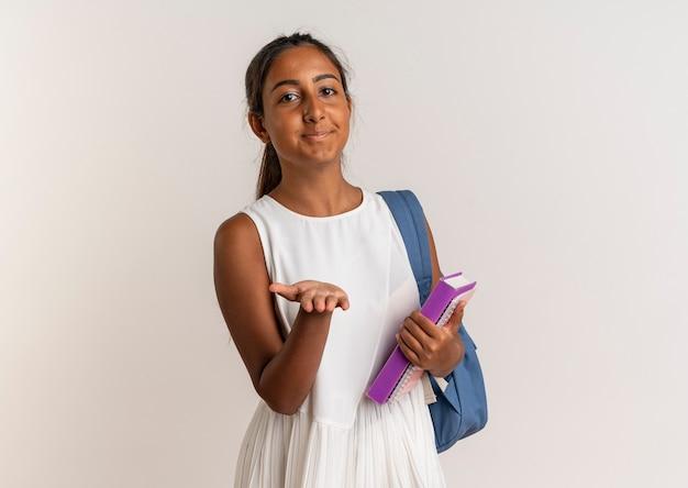 Erfreutes junges schulmädchen, das rückentasche hält buch hält und hand lokalisiert auf weißer wand hält