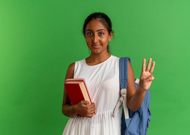 Erfreutes junges schulmädchen, das rückentasche hält buch mit notizbuch hält und mit hand drei auf grün zeigt