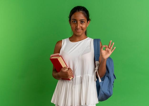 Erfreutes junges schulmädchen, das rückentasche hält buch mit notizbuch hält und okey geste auf grün zeigt