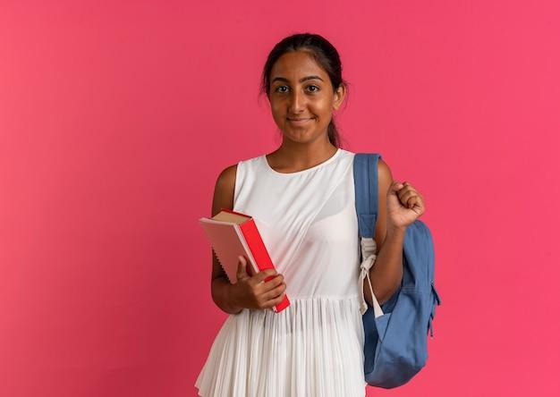 Erfreutes junges schulmädchen, das rückentasche hält buch und notizbuch zeigt ja geste