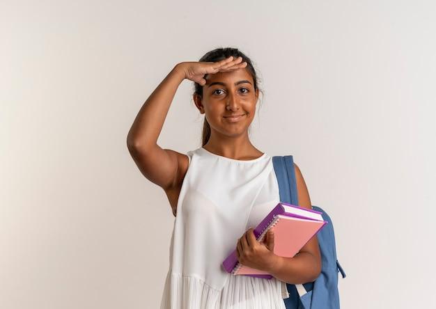Erfreutes junges schulmädchen, das rückentasche hält, notizbuch hält und abstand mit hand auf weiß betrachtet