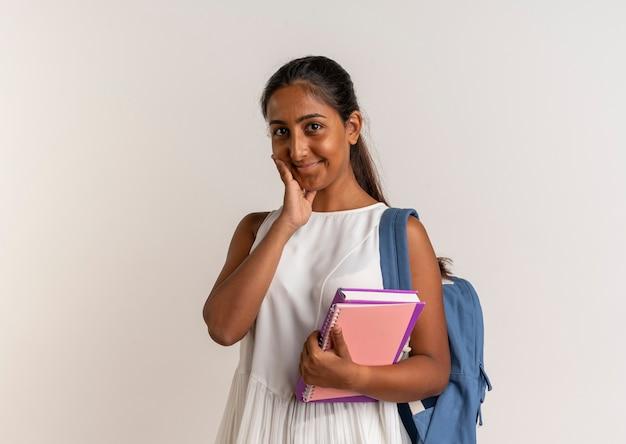 Erfreutes junges schulmädchen, das rückentasche hält, notizbuch hält und hand auf wange auf weiß legt