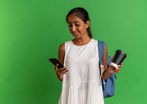 Erfreutes junges schulmädchen, das rückentasche trägt, die tasse kaffee hält und telefon in ihrer hand betrachtet
