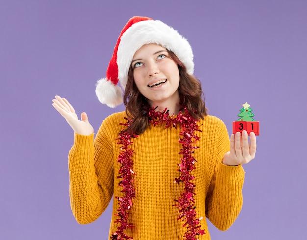 Erfreutes junges slawisches mädchen mit weihnachtsmütze und mit girlande um hals, der weihnachtsbaumverzierung hält und lokalisiert auf lila hintergrund mit kopienraum sucht