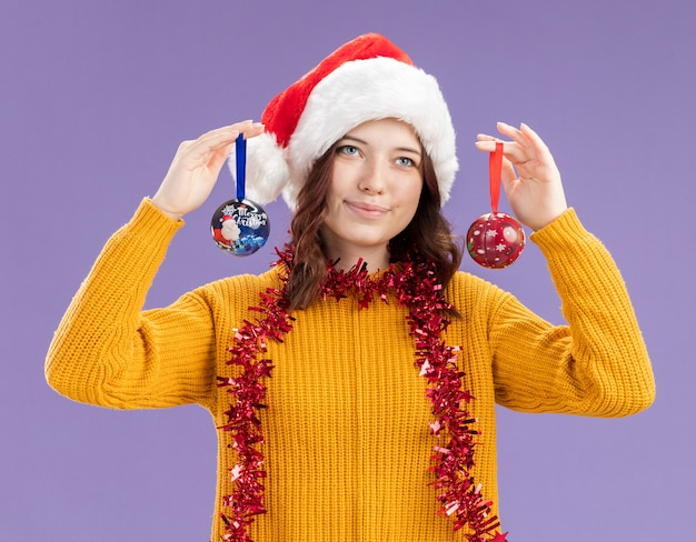 Erfreutes junges slawisches mädchen mit weihnachtsmütze und mit girlande um hals, die glaskugelverzierungen lokalisiert auf lila hintergrund mit kopienraum hält