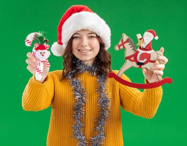 Erfreutes junges slawisches mädchen mit weihnachtsmütze und mit girlande um hals, die zuckerstange und weihnachtsmann auf schaukelpferdedekoration lokalisiert auf grünem hintergrund mit kopienraum hält