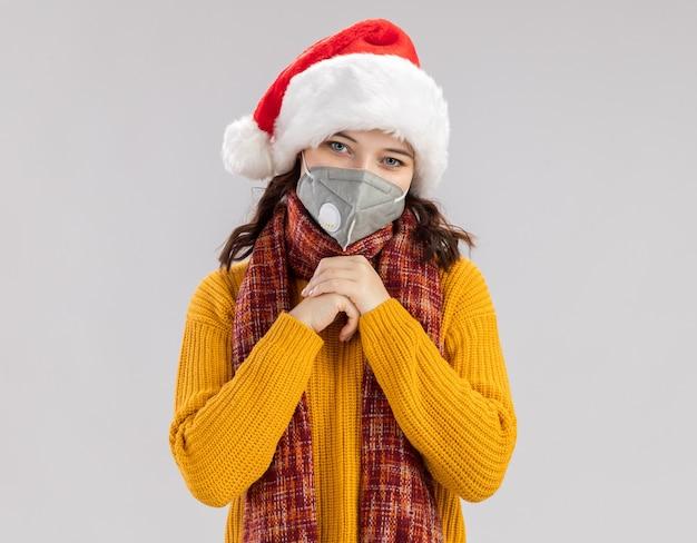 Erfreutes junges slawisches mädchen mit weihnachtsmütze und mit schal um den hals, das eine medizinische maske trägt und die hände zusammenhält, isoliert auf weißer wand mit kopierraum