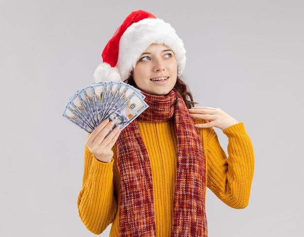 Erfreutes junges slawisches mädchen mit weihnachtsmütze und mit schal um den hals, das geld hält und die seite isoliert auf weißer wand mit kopienraum betrachtet