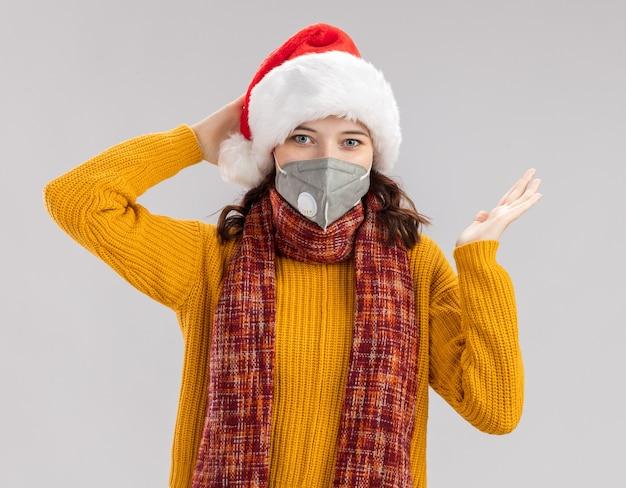 Erfreutes junges slawisches mädchen mit weihnachtsmütze und mit schal um hals, der medizinische maske trägt, hält hand offen auf weißem hintergrund mit kopienraum