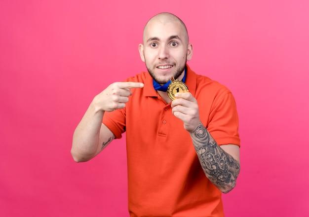 Erfreutes junges sportliches manntragen und zeigt auf medaille lokalisiert auf rosa wand