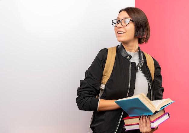 Erfreutes junges studentenmädchen, das brille und rückentasche hält bücher hält, die vor weißer wand stehen, die seite lokalisiert auf rosa wand betrachtet