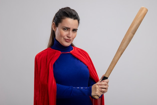 Erfreutes junges superheldenmädchen, das baseballschläger lokalisiert auf weiß hält