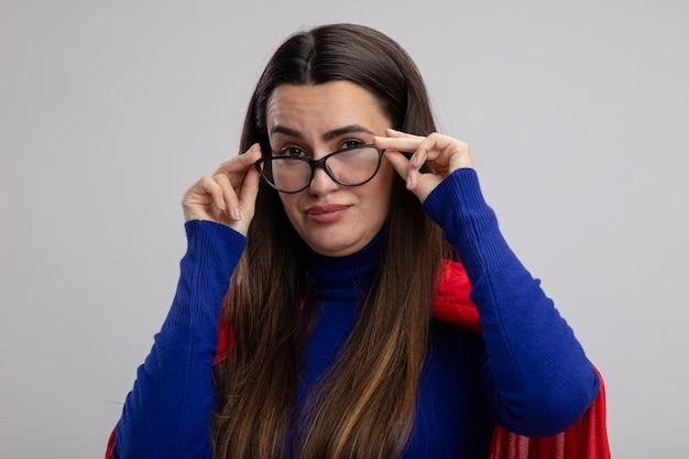 Erfreutes junges superheldenmädchen, das die auf weißem hintergrund isolierte und ergriffene brille trägt