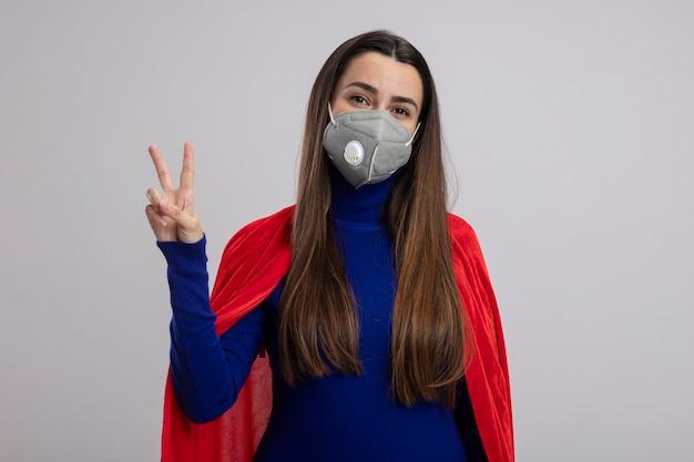 Erfreutes junges superheldenmädchen, das medizinische maske trägt, die friedensgeste lokalisiert auf weiß zeigt