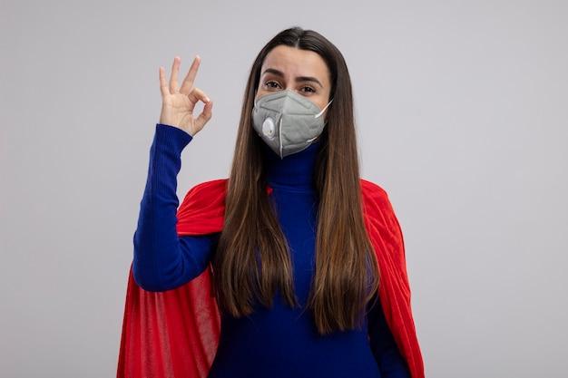 Erfreutes junges superheldenmädchen, das medizinische maske trägt, die okay geste lokalisiert auf weißem hintergrund zeigt