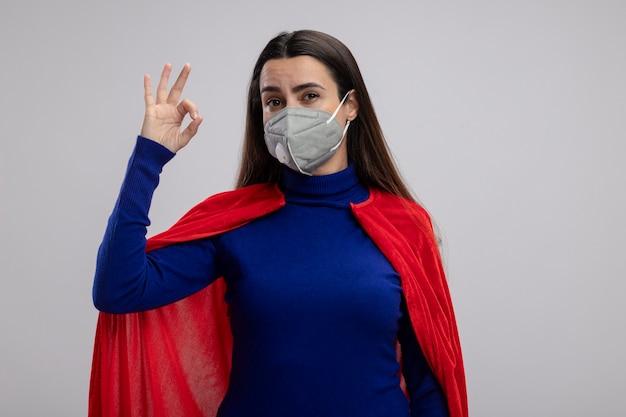 Erfreutes junges superheldenmädchen, das medizinische maske trägt und okay geste zeigt, die auf weiß isoliert wird