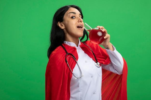 Erfreutes junges superheldenmädchen, das medizinisches gewand mit stethoskop hält und chemieglasflasche mit roter flüssigkeit gefüllt trägt, die auf grün isoliert wird