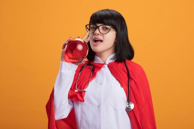 Erfreutes junges superheldenmädchen, das stethoskop mit medizinischem gewand und umhang mit gläsern trägt, trinkt rote flüssigkeit vom chemieglas