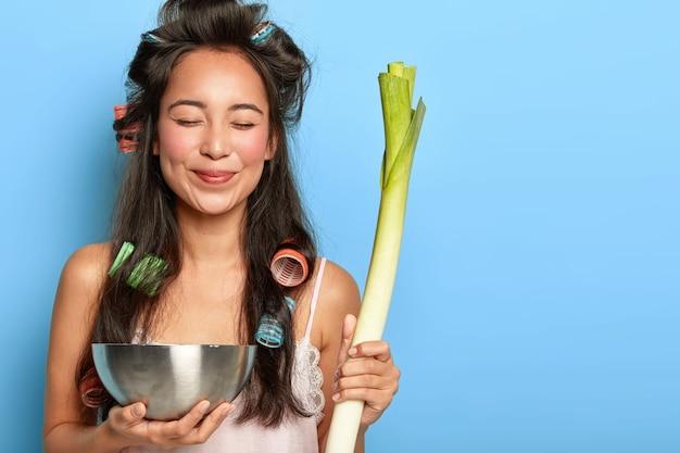 Erfreutes junges weibliches model mit lockenwicklern, trägt grünen lauch und eine schüssel, macht salat aus gesunden zutaten, hält die augen geschlossen