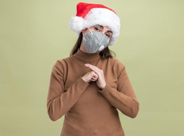 Erfreutes kippendes junges schönes mädchen des kippkopfes, das weihnachtshut mit der medizinischen maske hält, die hände zusammen lokalisiert auf olivgrünem hintergrund hält