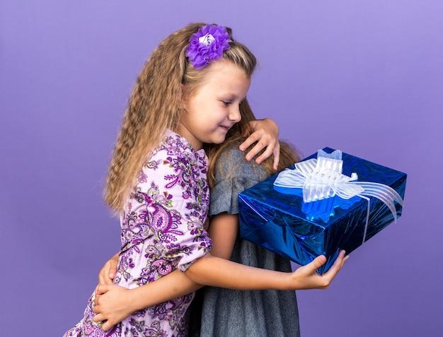 Erfreutes kleines blondes mädchen, das geschenkbox hält und ihre freundin isoliert auf lila wand mit kopienraum umarmt