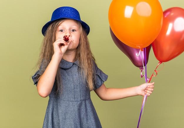 Erfreutes kleines blondes mädchen mit blauem partyhut, der heliumballons hält und partypfeife bläst, isoliert auf olivgrüner wand mit kopierraum