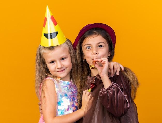 Erfreutes kleines blondes mädchen mit partymütze, das fröhliches kleines kaukasisches mädchen mit lila partyhut umarmt, das pfeife isoliert auf oranger wand mit kopierraum bläst